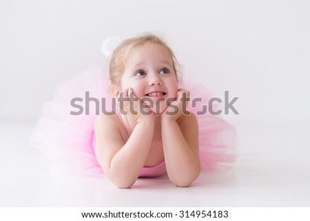 Little ballerina girl in a pink tutu. Adorable child dancing classical ballet in a white studio. Children dance. Kids performing. Young gifted dancer in a class. Preschool kid taking art lessons.