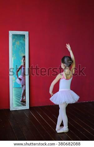 Little ballerina, young girl ballet dancer - Harmonious pretty preteen girl with tutu dancing and posing in loft studio - Contemporary dance performer - window shade - natural light near mirror - stock photo