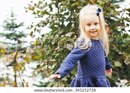 Little beautiful blonde girl with small blue bow in her hair wearing blue dress in park during walk on sunny summer autumn day. Young beautiful kid smiles and shows a bird pose. Copy space - stock photo