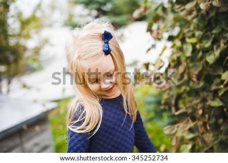Little beautiful blonde girl with small blue bow in her hair wearing blue dress in park during walk on sunny summer autumn day. Young beautiful shy kid looking downwards - stock photo