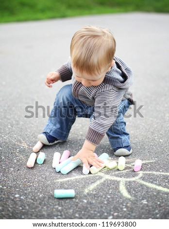 little beautiful boy draws with chalk on asphalt - stock photo
