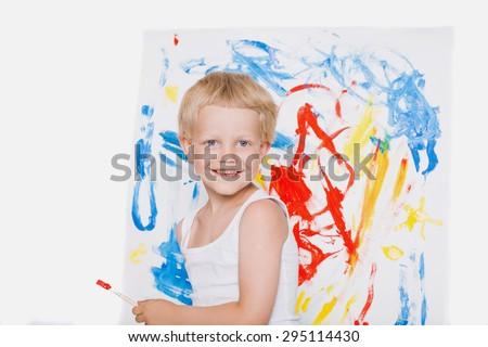 Little beautiful boy paints a picture. School. Preschool. Education. Creativity. School. Education. Creativity. Studio portrait over white background - stock photo