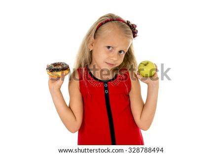 little beautiful female child with blond hair choosing dessert holding unhealthy but tasty chocolate donut and apple fruit in healthy versus unhealthy die nutrition isolated on white background - stock photo