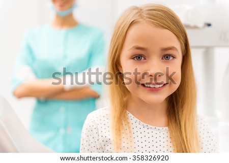 Little beautiful girl at the dentist looking at the camera and smiling - stock photo