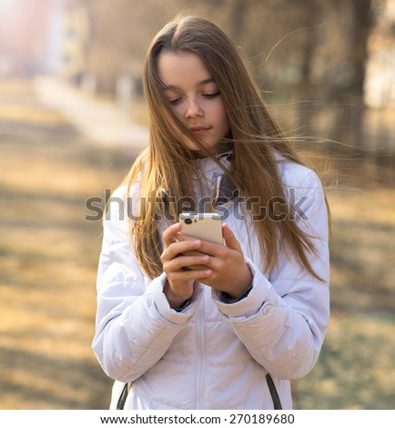 Little beautiful girl brunette standing on the street in spring or autumn in a white jacket, holding a phone and dials a message on social networks - stock photo