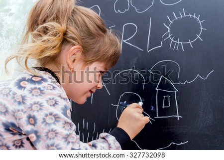Little beautiful girl drawing on a blackboard. Learning at Home. - stock photo