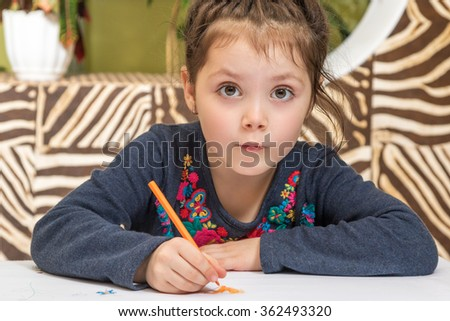 Little beautiful girl draws pencil sitting at the table and looking at the camera with eyes wide open - stock photo