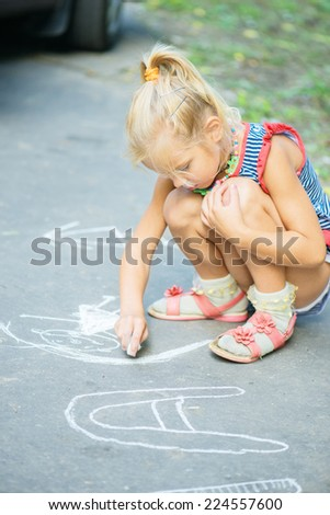 Little beautiful girl draws with chalk on pavement in summer city park. - stock photo