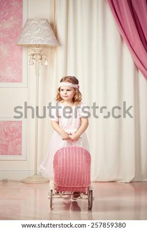 Little beautiful girl game with pram - stock photo