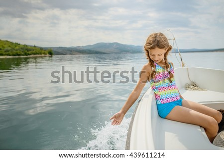 Little beautiful girl goes on a launch on the Adriatic Sea along the coast of Croatia. - stock photo
