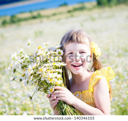 Little beautiful girl holding bouquet of daisies standing in field