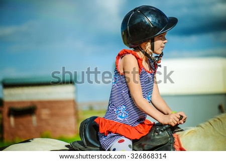 Little beautiful girl in a helmet riding a horse. - stock photo