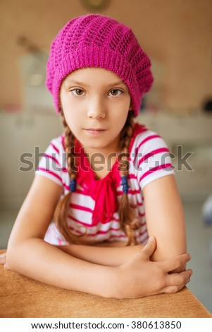 Little beautiful girl in a red beret sitting at the kitchen table. - stock photo