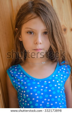 Little beautiful girl in blue dress near the wooden wall. - stock photo