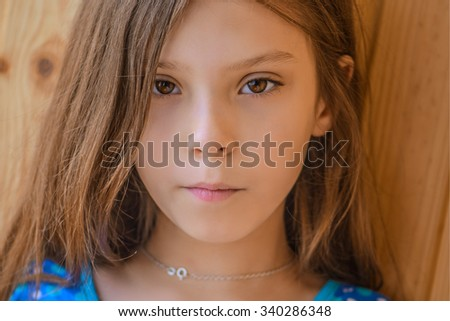 Little beautiful girl in blue dress near the wooden wall. - stock photo