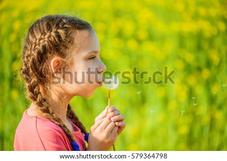 Little beautiful girl in red dress blows on dandelion on background of green summer park.