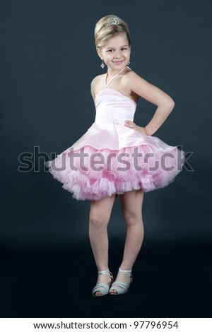 Little beautiful girl in the fashion pink dress - stock photo