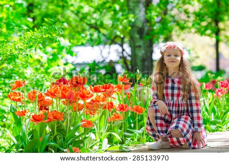 Little beautiful girl in tulips garden at warm spring day - stock photo