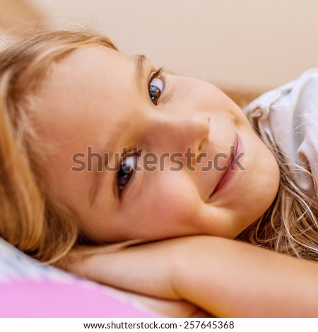 Little beautiful girl lying on bed before sleeping and smiling. - stock photo