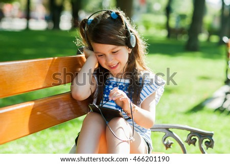 Little beautiful girl playing in the park game pad