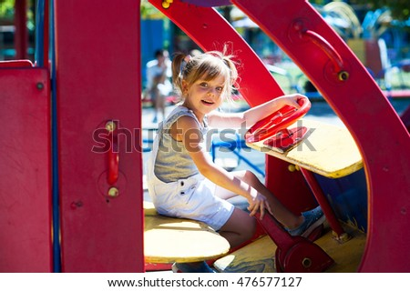 Little beautiful girl playing in the playground