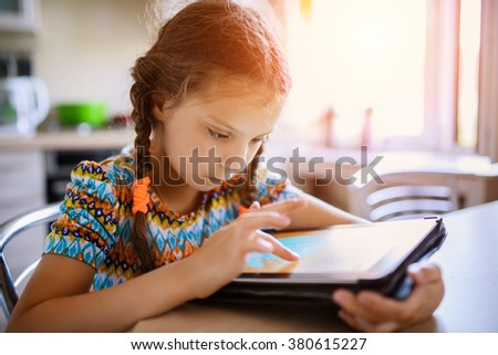 Little beautiful girl running on the tablet, sitting at the kitchen table.