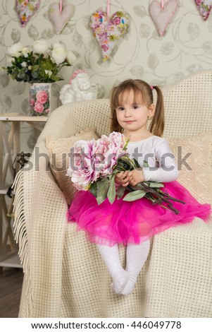 Little beautiful girl sitting in a ballerina costume with a bouquet of peonies - stock photo