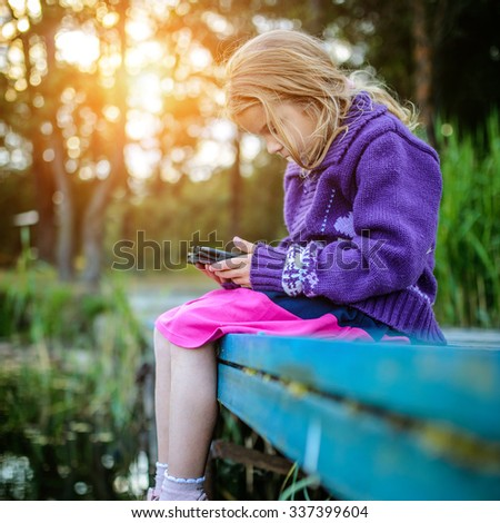 Little beautiful girl sitting on a river pier, and read e-books. - stock photo