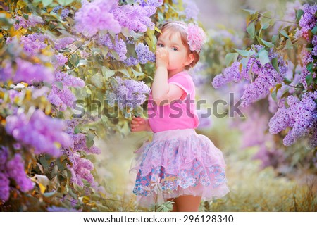 Little beautiful  girl standing in the lilac park on a sunny morning and smiling.