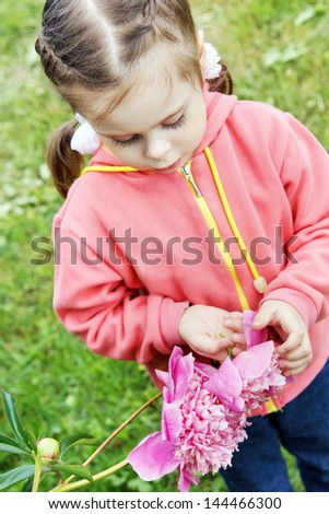 Little beautiful girl with big peony flower in the garden - stock photo