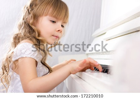 little beautiful girl with blond long curls in white dress playing on white piano  - stock photo