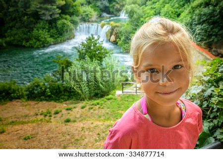 Little beautiful girl with curly hair close-up against the background of a waterfall River KRKA in Croatia. - stock photo