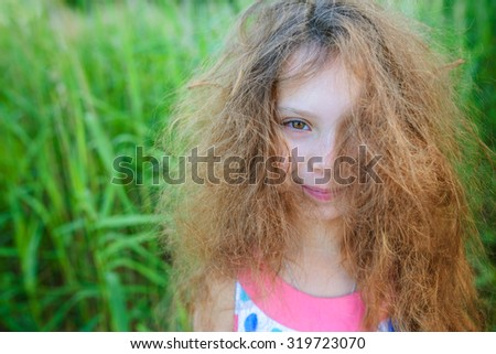 Little beautiful girl with curly hair close-up on a background of green garden. - stock photo