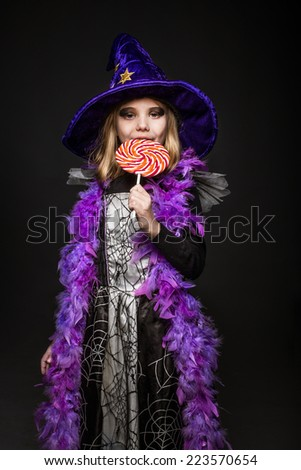 Little beautiful girl with halloween witch costume eat colored candy. Studio portrait over black background - stock photo