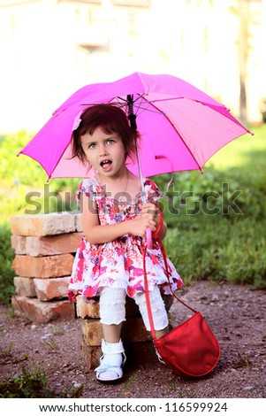 little beautiful girl  with pink umbrella and handbag in park
