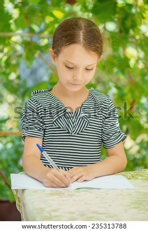 Little beautiful girl writes in notebook on background of summer infield. - stock photo