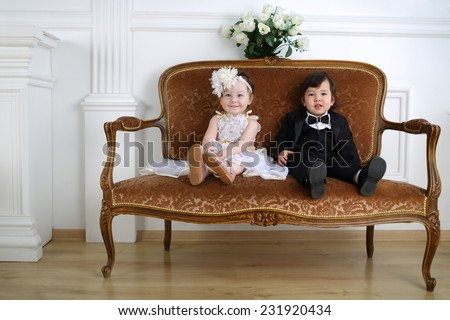 Little beautiful lady in white long dress and her friend in black suit sitting on couch - stock photo