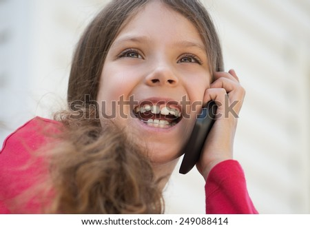 Little beautiful laughing girl in red jacket talking on cell phone. - stock photo