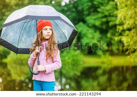 Little beautiful pensive girl in red cap and an umbrella on background of autumn park with lake. - stock photo