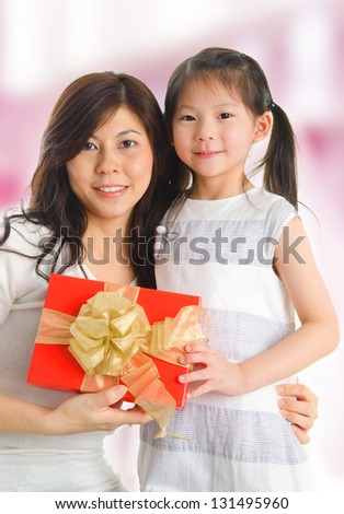 Little beautiful pretty Asian girl giving a gift to her happy mother - indoors. - stock photo