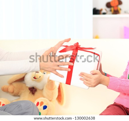 Little beautiful pretty girl giving a gift to her happy mother - stock photo
