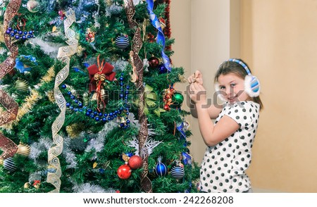 little beautiful pretty happy girl decorating and preparing a Christmas tree in her room  - stock photo