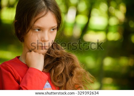 Little beautiful sad girl in red clothes thought, against green summer park. - stock photo