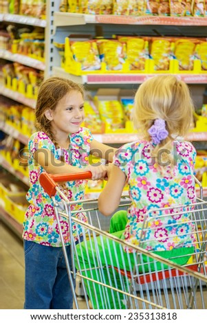 Little beautiful sisters in modern supermarket with cart. - stock photo