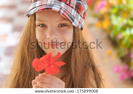 Little beautiful smiling girl holding red flower, summer in city park.