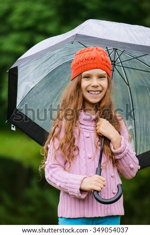 Little beautiful smiling girl in a red cap and pink sweater holding umbrella on a background of green park.