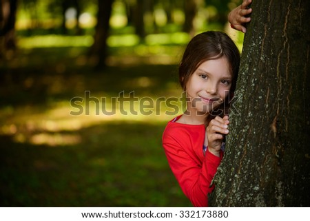 Little beautiful smiling girl in a red dress is hiding behind a tree in the park. - stock photo