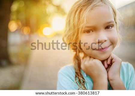 Little beautiful smiling girl on a background of a sunset on a city street.
