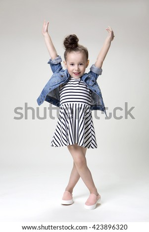 Little beautiful smiling girl with a funny face in a striped dress and denim jacket posing  on a light background in studio - stock photo