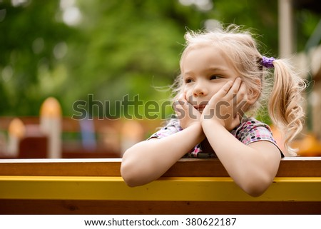 Little beautiful thoughtful girl sitting on the bench in summer green city park.